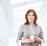 A young brunette businesswoman holding a cup Stock Images