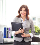 A young brunette businesswoman holding a folder Stock Image