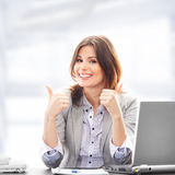 A young brunette businesswoman holding thumbs up Stock Photography