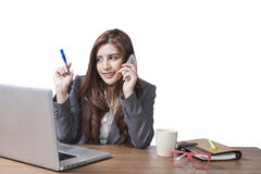 Young brunette businesswoman sitting talking mobile phone at her Stock Photography