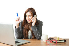 Young brunette businesswoman sitting talking mobile phone at her Royalty Free Stock Photography