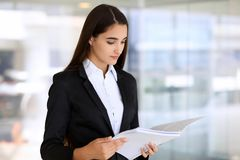 Young brunette businesswoman or student girl looking at camera.  Stock Photo