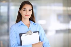 Young brunette businesswoman or student girl looking at camera.  Stock Photos
