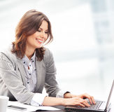 A young brunette businesswoman working on a laptop Stock Photos