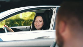 Young brunette in the car talking with a man from the neighboring car. In traffic on road stock video