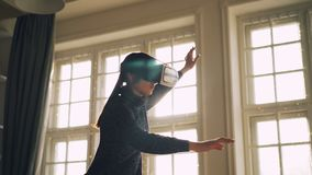 Young brunette is using augmented reality glasses at home moving hands and body standing in room alone enjoying modern. Young brunette in casual clothing is stock video