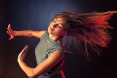 Young brunette caucasian woman dancing and her hair flowing through the air Stock Photos