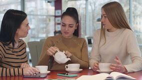 Young brunette Caucasian woman pouring tea into cups and talking with female friends. Three beautiful girls resting in