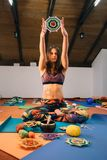 Female yoga instructor showing knitted mandala in class. Young brunette caucasian yoga instructor with henna tattoo holding mandala high while sitting in lotus Stock Photos