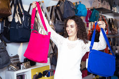 Young brunette choosing bag among assortment in store Stock Photography