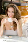 Young brunette in coffee shop. Royalty Free Stock Image