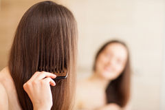 Young brunette combing her hair Royalty Free Stock Images