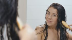 Young brunette combs wet hait in front of mirror in bathroom after shower stock video footage