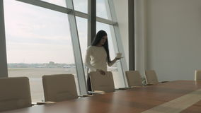 Young brunette in the conference hall of the airport. Pretty brunette is in the conference hall of the airport. Young female pushes the chairs at the table stock video footage