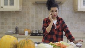 Young womann talks on phone while cooking the dinner at the kitchen. Young brunette cooks dinner at kitchen and talks on phone. She stands near the table with stock video