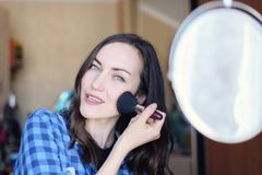 Young brunette corrects make-up at the round mirror in the bedroom.  Stock Photography