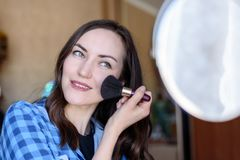 Young brunette corrects make-up at the round mirror in the bedroom.  Stock Photo