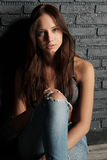 Young brunette in crop top and ripped jeans sitting on the floor leaning against the brick wall. Vertical photo Royalty Free Stock Photography