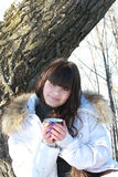 Young brunette with a cup of tea resting in the forest. Beautiful young brunette with a cup of tea near the tree Royalty Free Stock Photo