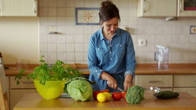 A young brunette is cutting vegetables for a salad. He tries carrots and dances fun. We cook ourselves. Home cooking stock footage