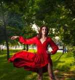 Young brunette dancing in red dress outdoors on nature backgroun Royalty Free Stock Photography
