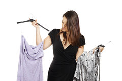 Young brunette deciding what to wear. Isolated on white Stock Photos