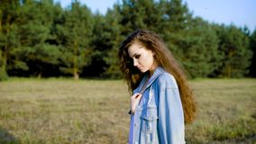 Young brunette in denim posing sensually on background of trees in field. Trendy young woman in denim jacket standing in summer field stock video footage