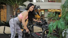 Young brunette is doing dumbbell row exercise in sports club. Woman takes quickly free weight, leans on rack with arm, tilts body and pulls iron device up stock video