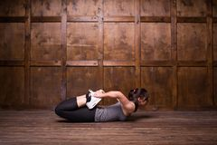 Fitness and exercice concept. Young brunette doing exercise on floor. Isolated on wooden background Royalty Free Stock Images