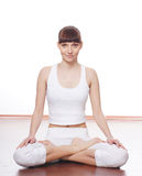 A young brunette doing yoga in white clothes Stock Photo