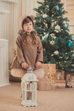 Young brunette dolly lady girl stylish dressed cozy warm winter gray jacket with fur posing sitting standing in studio close to Ch. Ristmas New Year tree and Royalty Free Stock Image