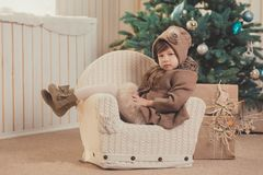 Young brunette dolly lady girl stylish dressed cozy warm winter gray jacket with fur posing sitting standing in studio close to Ch. Ristmas New Year tree and Royalty Free Stock Images