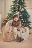 Young brunette dolly lady girl stylish dressed cozy warm winter gray jacket with fur posing sitting standing in studio close to Ch. Ristmas New Year tree and Stock Photos