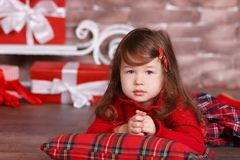 Young brunette dolly lady girl stylish dressed in red dress costume chequers check tartan skirt strap shoes smiling posing sitting. In studio christmas tree Royalty Free Stock Photos