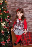 Young brunette dolly lady girl stylish dressed in red dress costume chequers check tartan skirt strap shoes smiling posing sitting. In studio christmas tree Stock Images