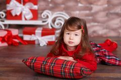 Young brunette dolly lady girl stylish dressed in red dress costume chequers check tartan skirt strap shoes smiling posing sitting. In studio christmas tree Stock Image