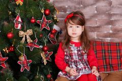 Young brunette dolly lady girl stylish dressed in red dress costume chequers check tartan skirt strap shoes smiling posing sitting. In studio christmas tree Royalty Free Stock Images