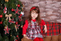Young brunette dolly lady girl stylish dressed in red dress costume chequers check tartan skirt strap shoes smiling posing sitting. In studio christmas tree Stock Photography