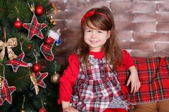 Young brunette dolly lady girl stylish dressed in red dress costume chequers check tartan skirt strap shoes smiling posing sitting. In studio christmas tree Stock Photo