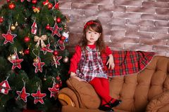 Young brunette dolly lady girl stylish dressed in red dress costume chequers check tartan skirt strap shoes smiling posing sitting. In studio christmas tree Stock Photos