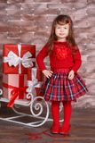 Young brunette dolly lady girl stylish dressed in red pullover sweater chequers check tartan skirt strap shoes smiling posing sitt. Ing in studio winter sledge Royalty Free Stock Photos