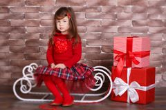 Young brunette dolly lady girl stylish dressed in red pullover sweater chequers check tartan skirt strap shoes smiling posing sitt. Ing in studio winter sledge Royalty Free Stock Photography