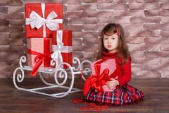 Young brunette dolly lady girl stylish dressed in red pullover sweater chequers check tartan skirt strap shoes smiling posing sitt. Ing in studio winter sledge Royalty Free Stock Images