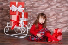 Young brunette dolly lady girl stylish dressed in red pullover sweater chequers check tartan skirt strap shoes smiling posing sitt. Ing in studio winter sledge Stock Images