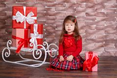 Young brunette dolly lady girl stylish dressed in red pullover sweater chequers check tartan skirt strap shoes smiling posing sitt. Ing in studio winter sledge Royalty Free Stock Image