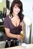 Young brunette draws beer at the bar Royalty Free Stock Photography