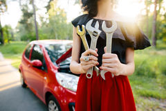 Young brunette in a dress repairs a red car with a wrench Stock Images