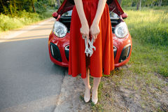 Young brunette in a dress repairs a red car with a wrench Stock Photo