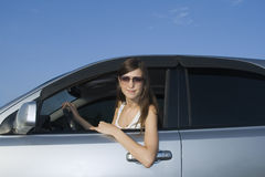 Young brunette driving silver car Stock Images