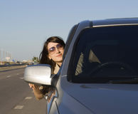 Young brunette driving silver car Royalty Free Stock Image